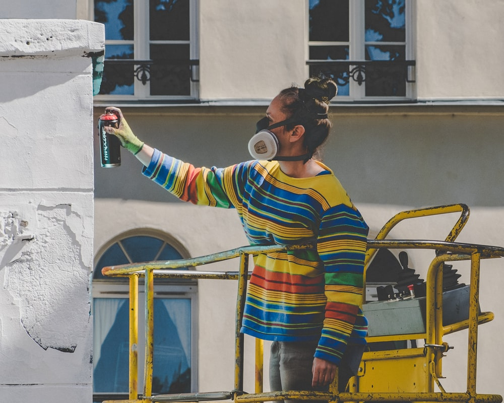 woman spraying paint during daytime