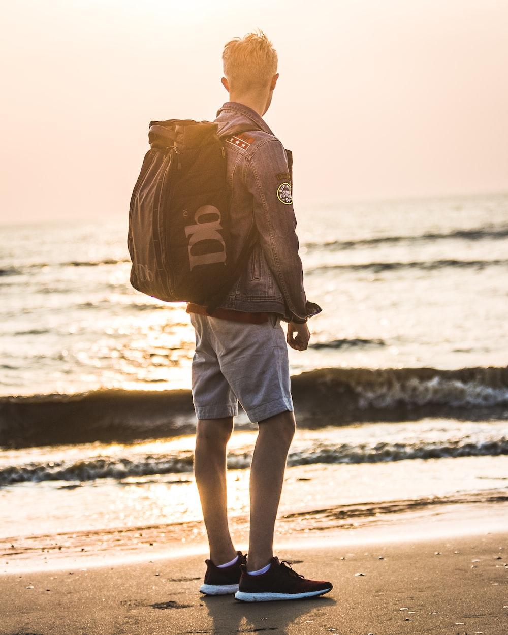 man carrying backpack standing near shoreline
