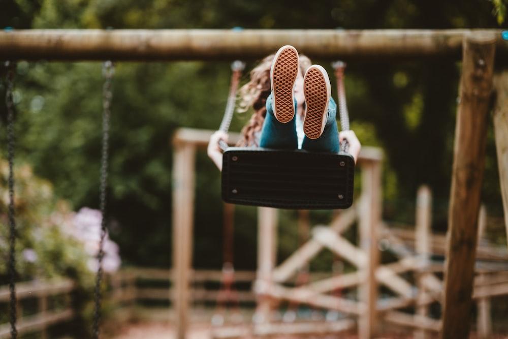 woman riding swing near trees