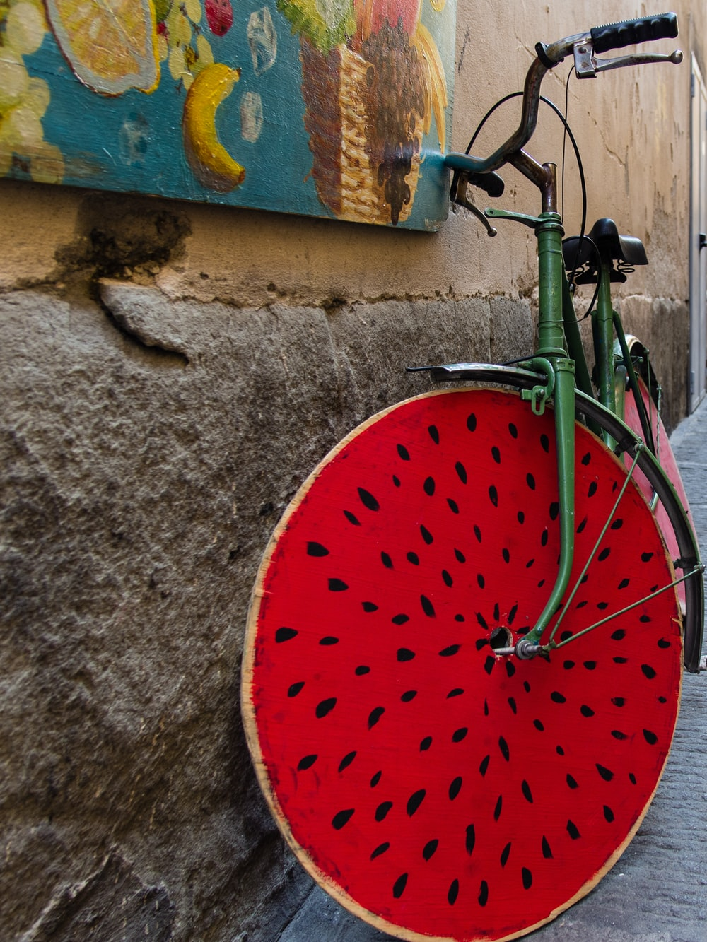 green and red bicycle parked beside concrete wall