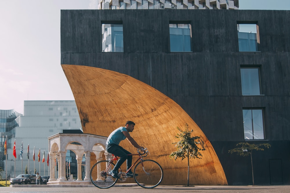 man riding bicycle near building