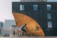 man riding bicycle near building