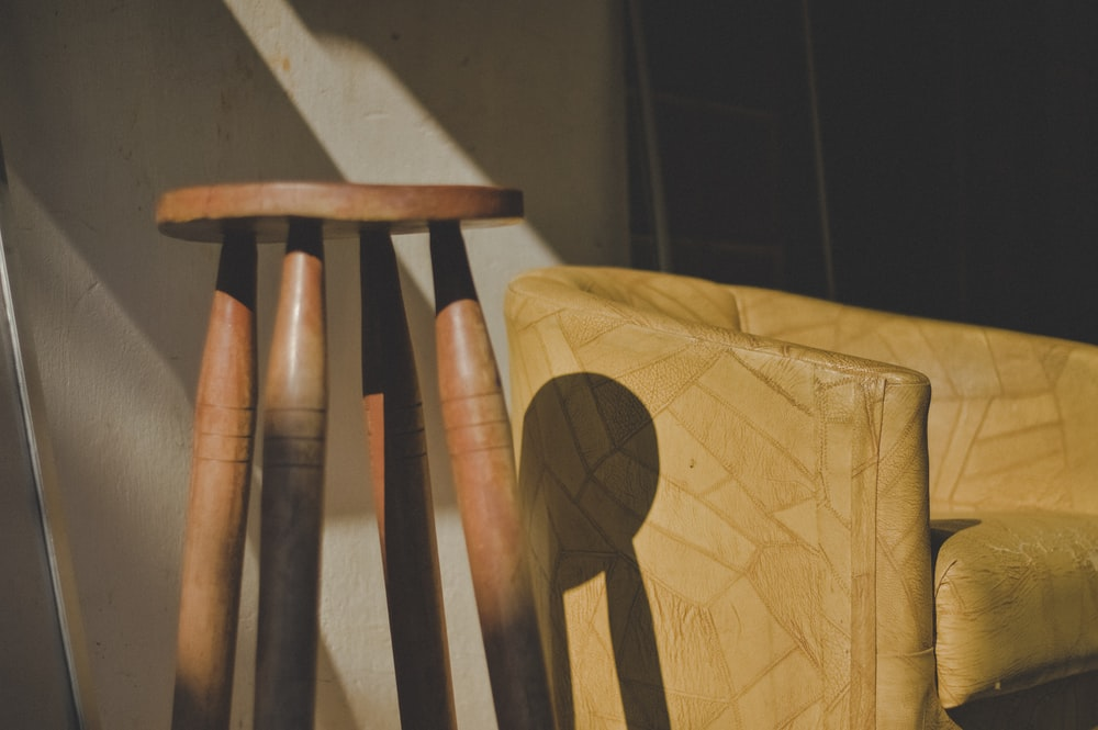 brown wooden stool near barrel chair