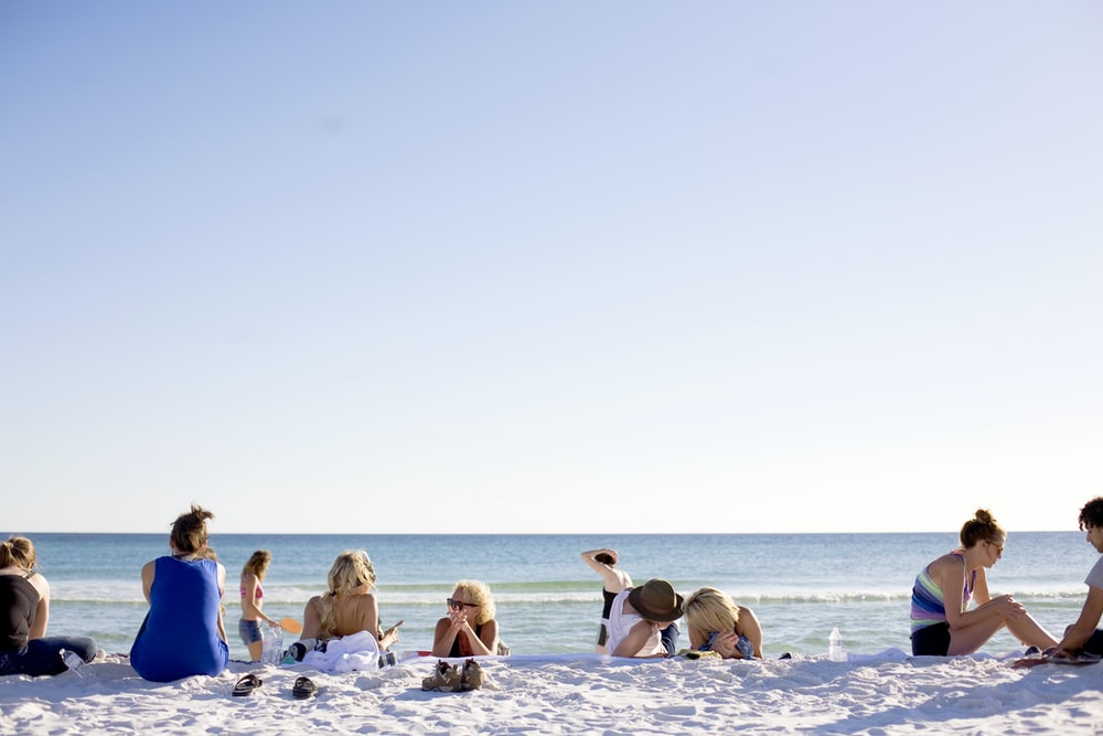 people on white sands by the beach