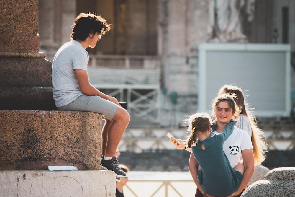 man sitting beside pillar facing two women and girl