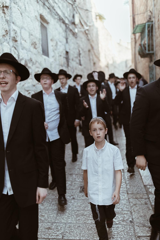 group of men walking on concrete road
