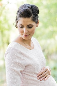 selective focus photography pregnant woman looking down white holding her tummy
