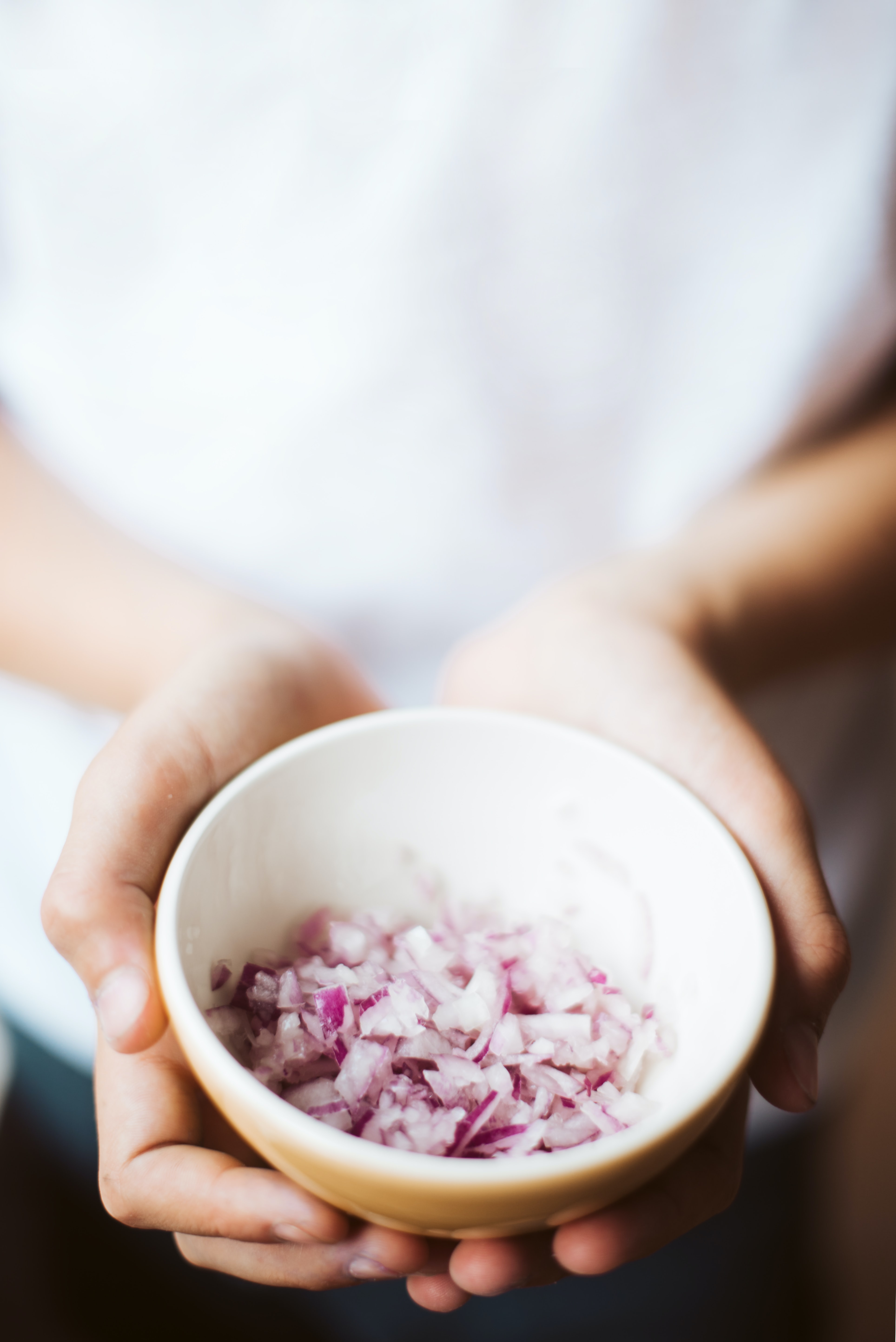 person holding ceramic bowl filled with onions