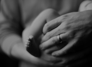 grayscale photo of person holding baby