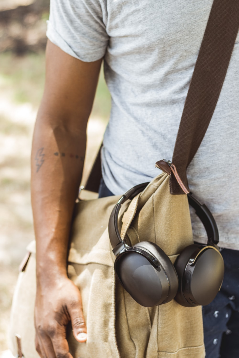man wearing brown crossbody bag with headphones hanged
