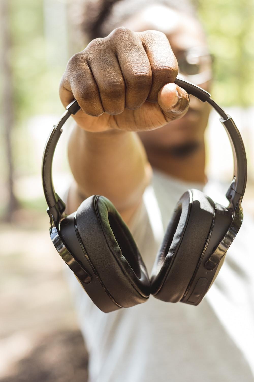 man holding wireless headphones