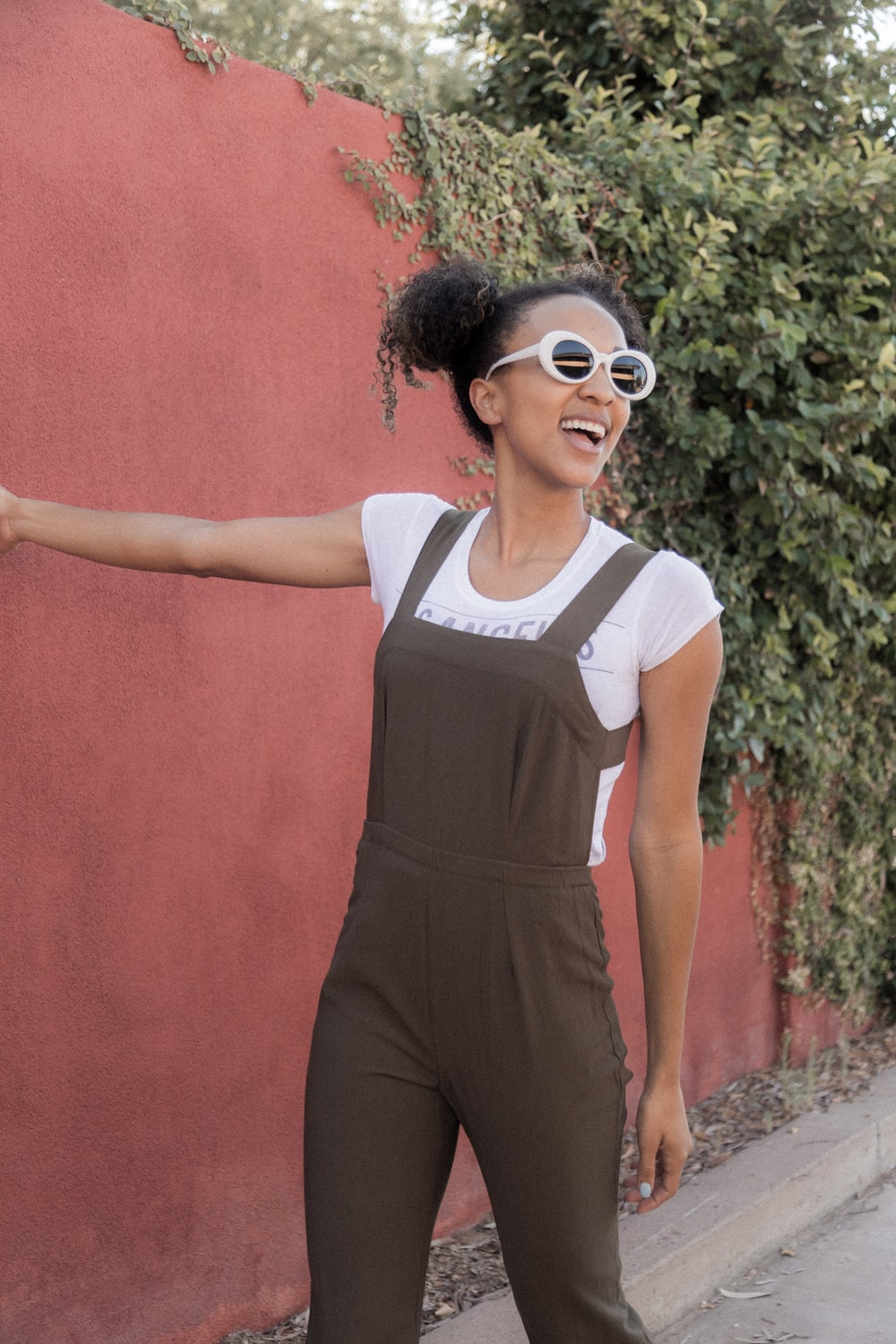 woman wearing white framed sunglasses walking near brown wall at daytime