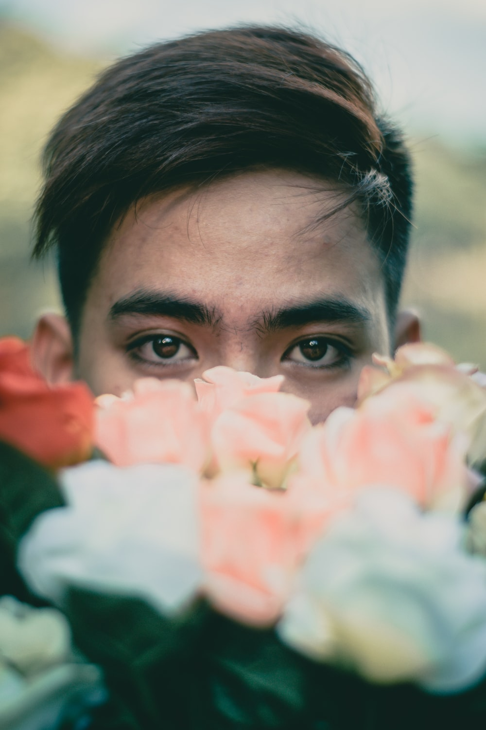 man hiding behind pink and white flowers