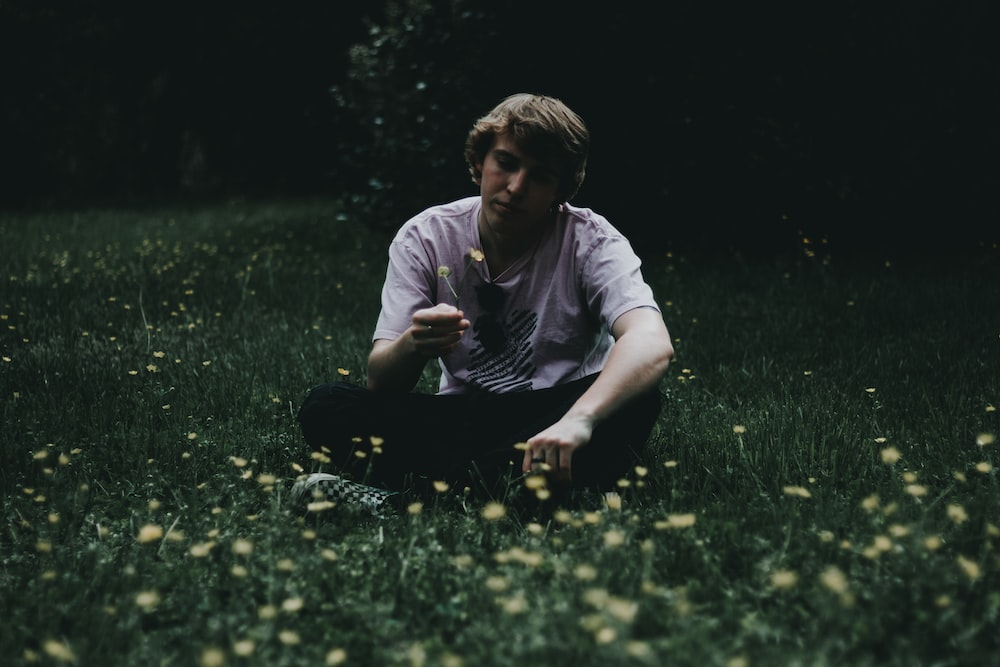 man holding flower while sitting on green grass field