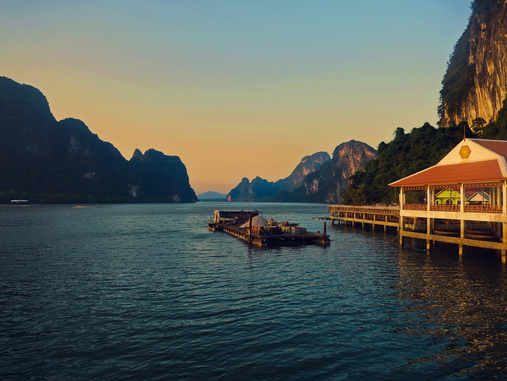 floating restaurant on body of water near mountains