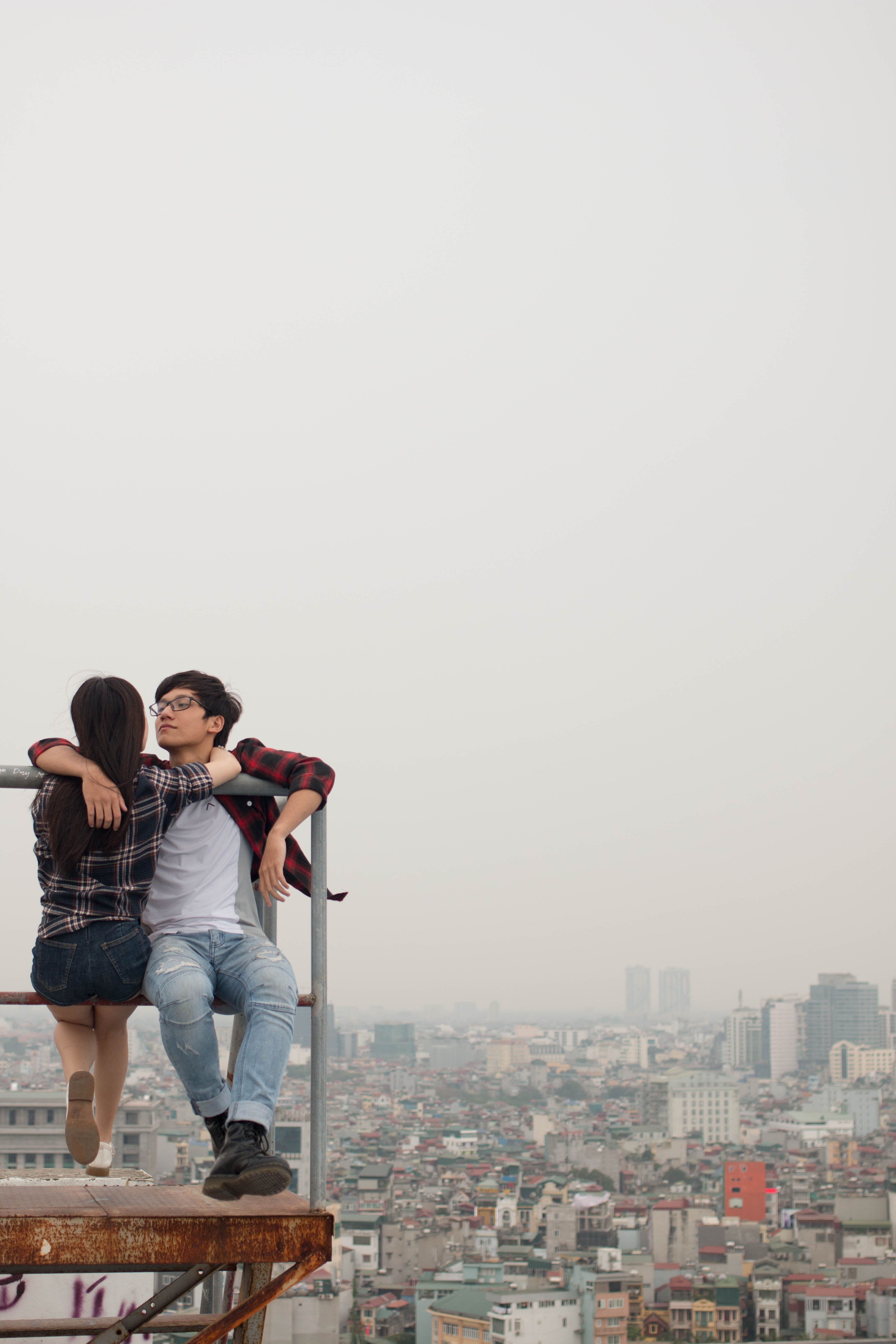 man and woman sitting on metal tube at building top