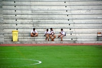 four boys wearing white shirt sitting near field