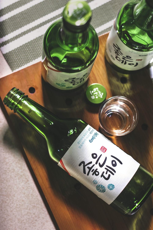 three Kanji script text bottles on wooden panel