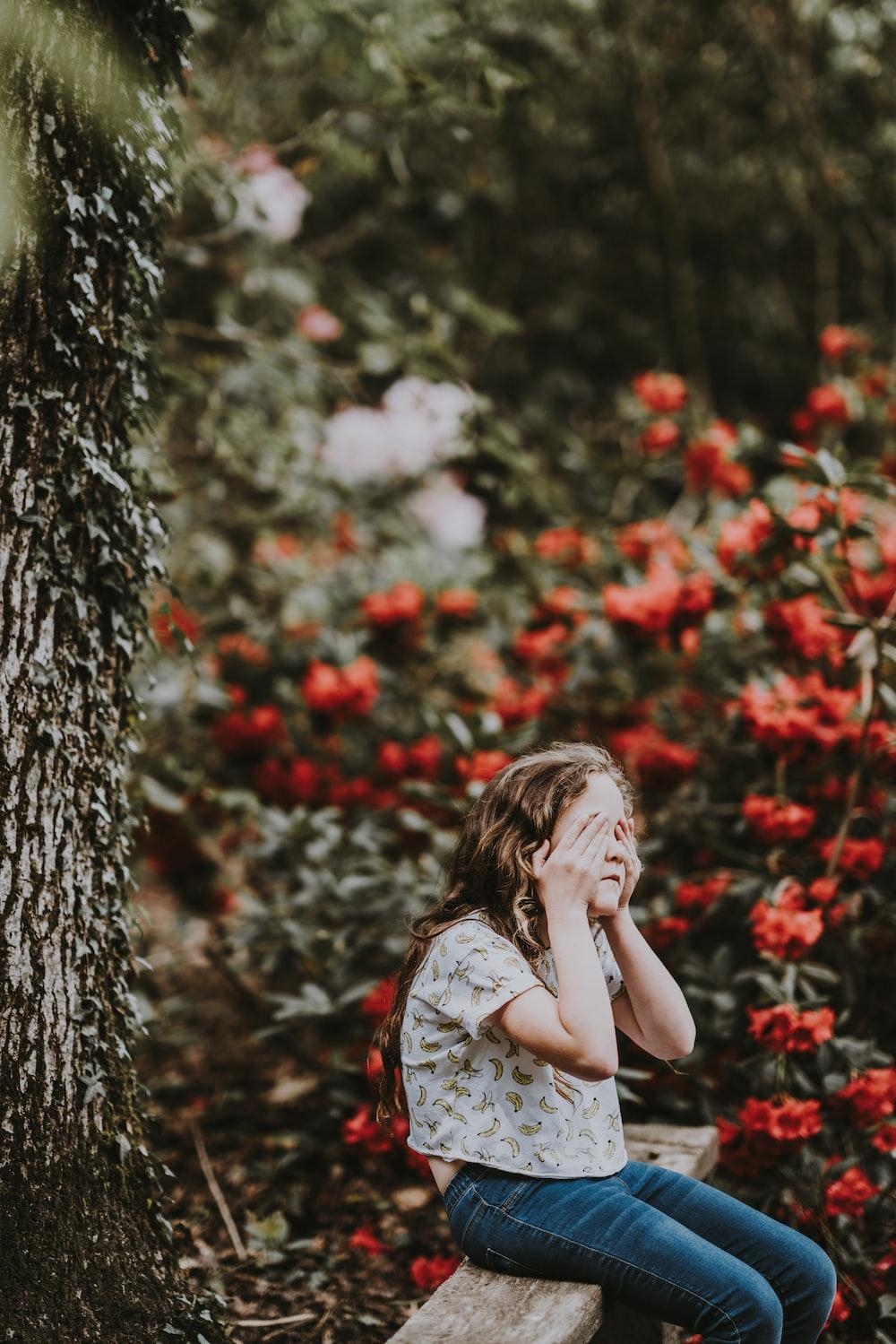 girl sitting on wooden bench near flowers