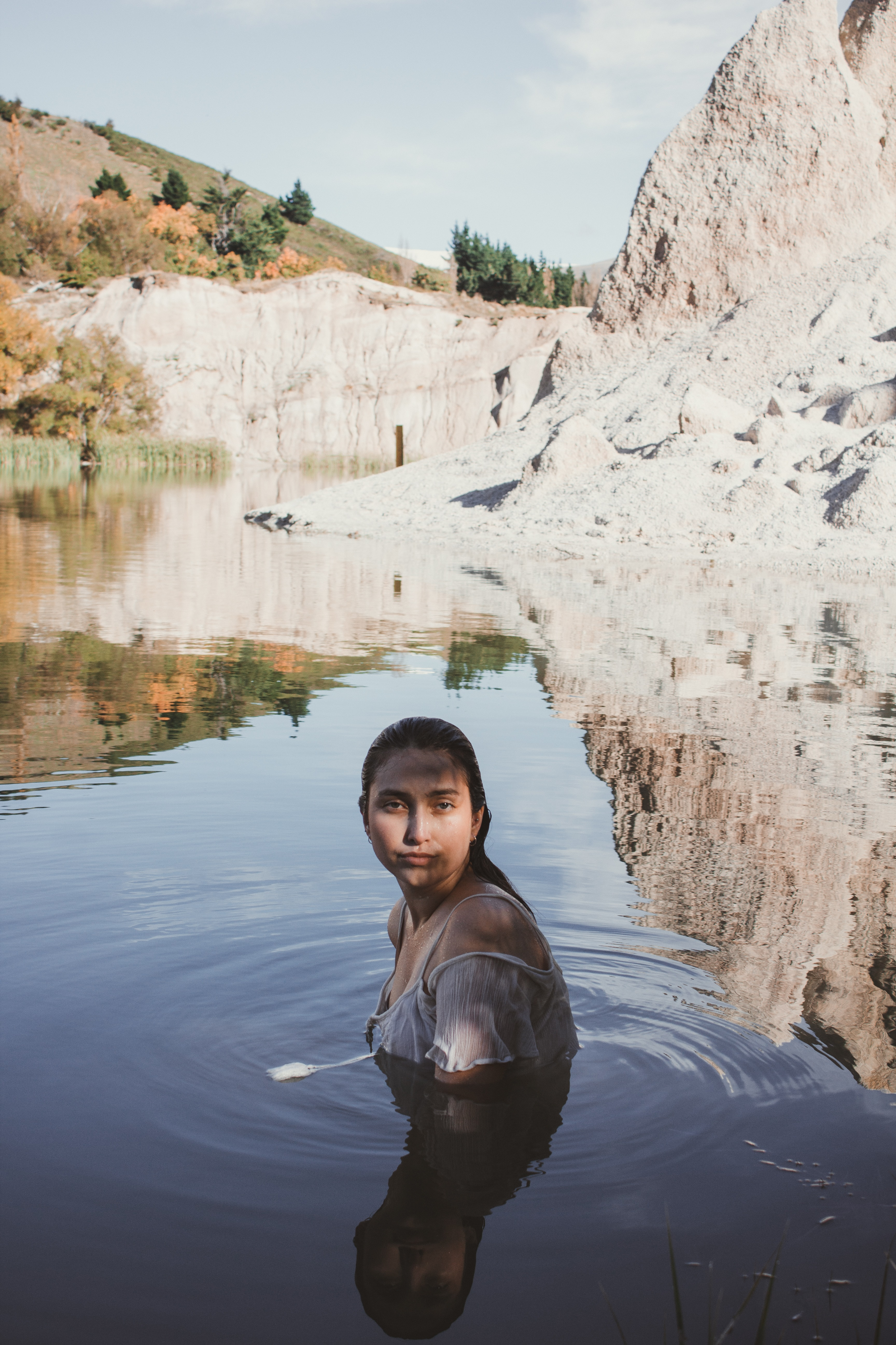 woman in body of water beside rocky mountain during daytime