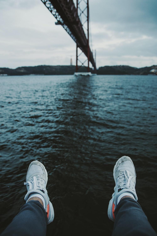 person sitting beside body of water under bridge