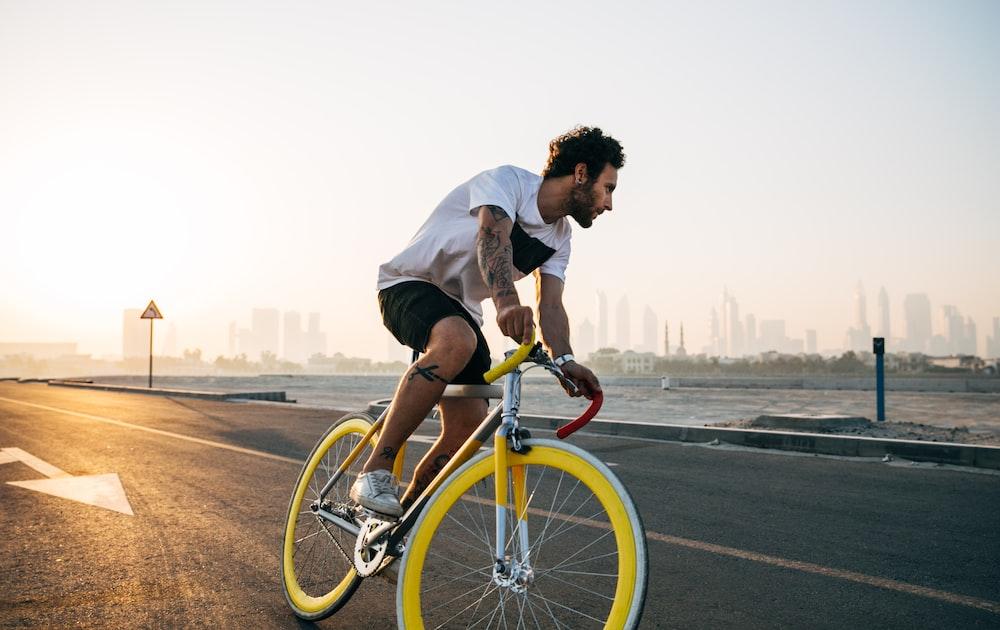 man riding bicycle on road during daytime