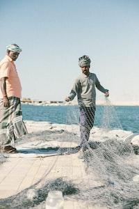 man holding fish net near sea