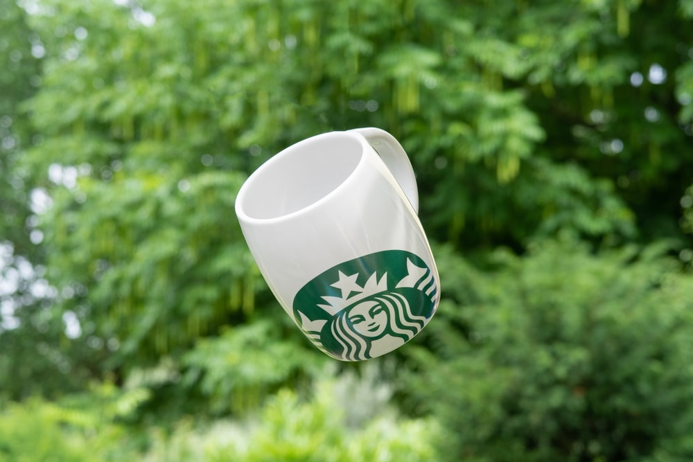 selective focus photography of floating white and green Star Bucks ceramic mug