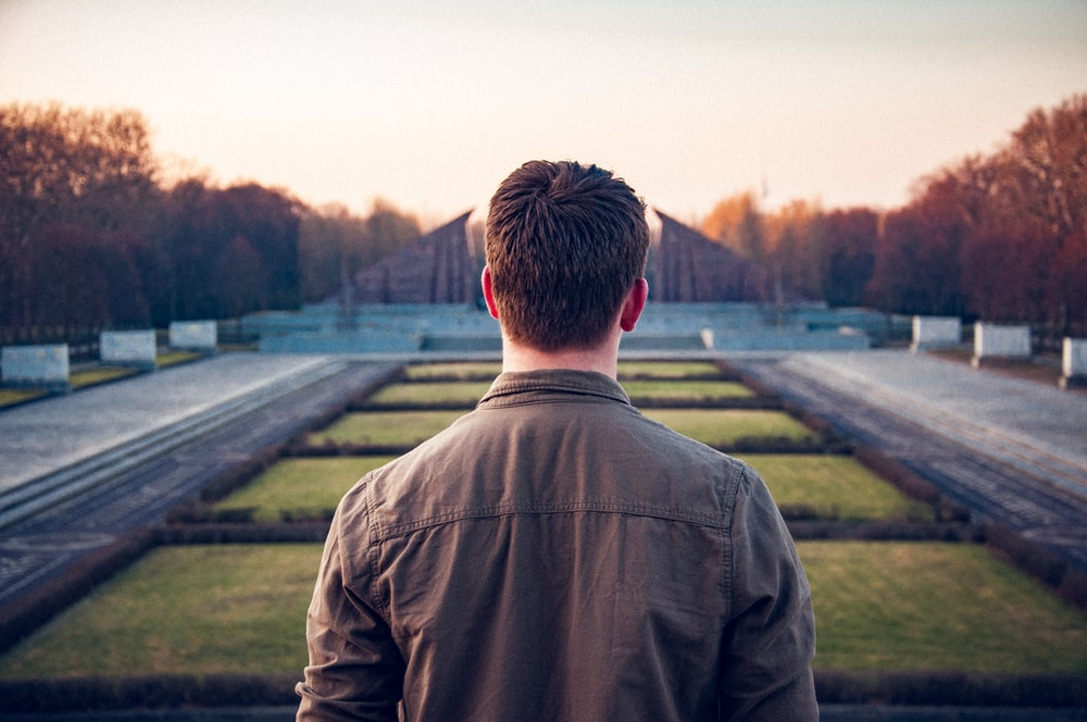 man standing between pathway during daytime