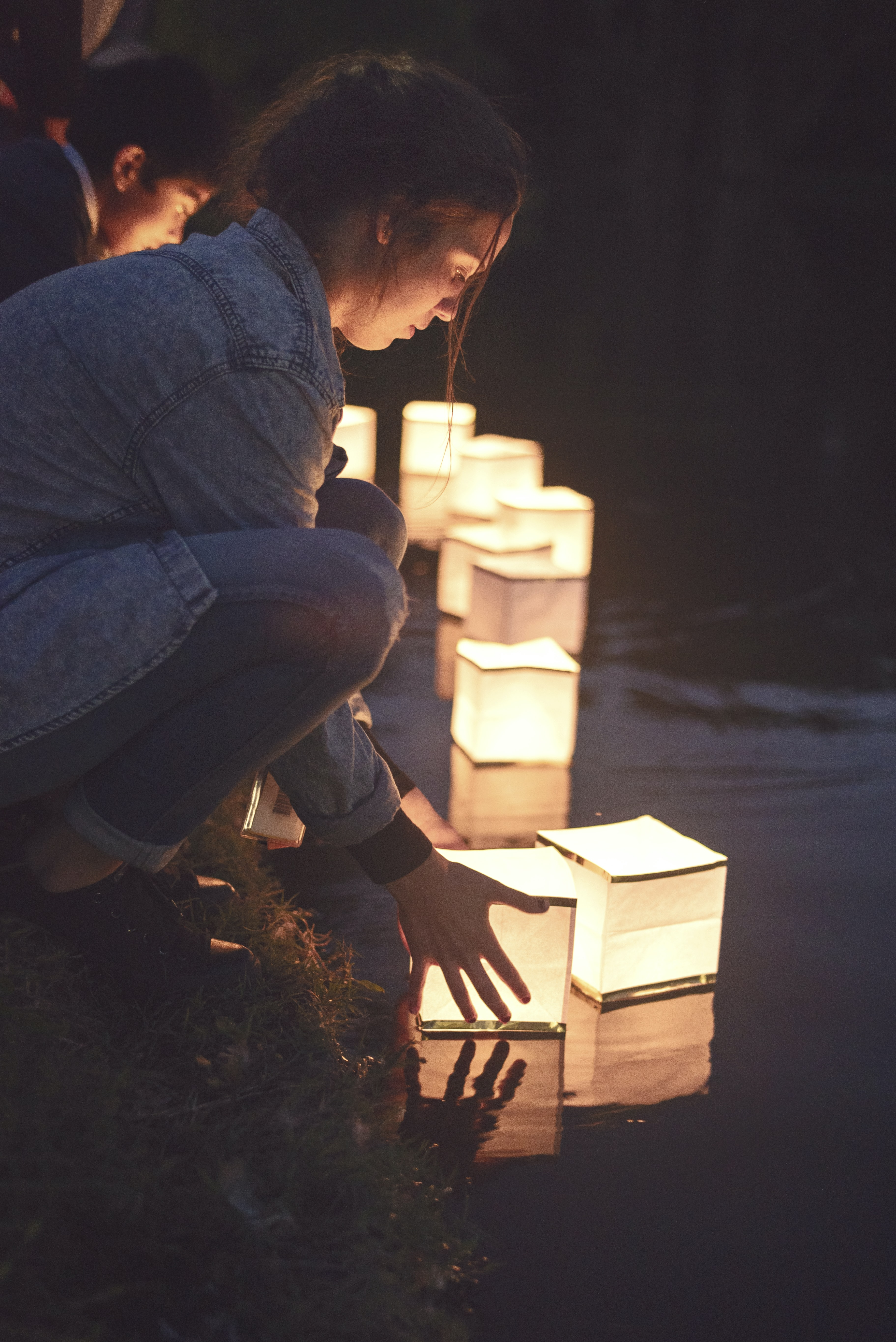 woman placing lighted floating candles on water