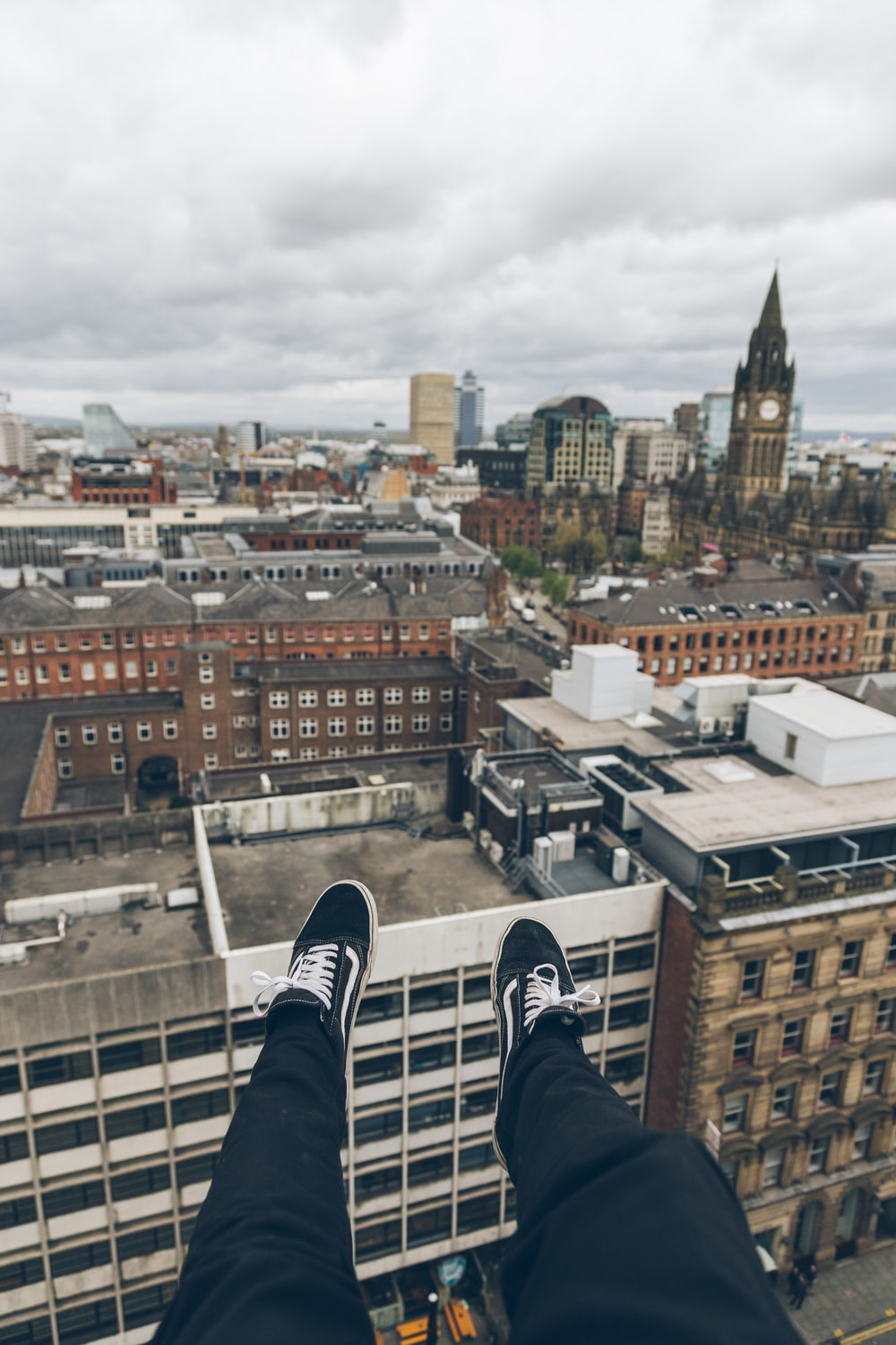 person sitting on edge of building rooftop