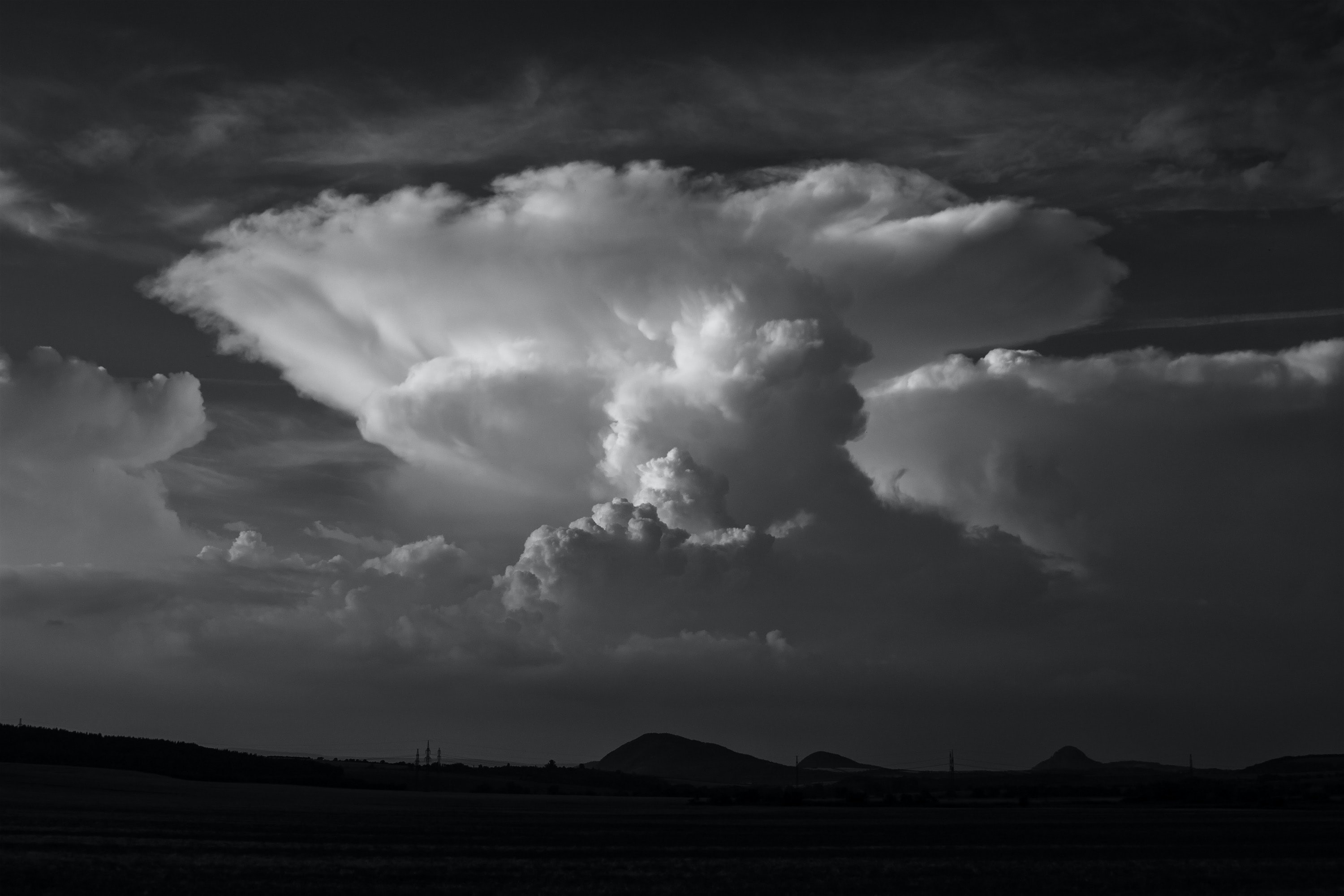 black and white photo of clouds above mountain thunderhead
