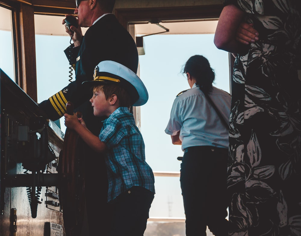 boy in plaid top wearing ship captain hat