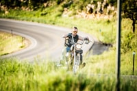 selective focus photography of man riding black chopper motorcycle
