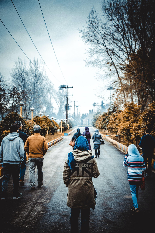 people walking on gray road at daytime