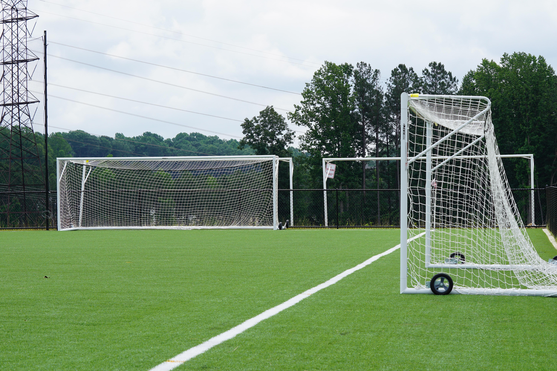 three white goal nets on grass field