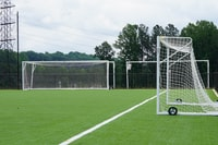 three white goal nets on grass field