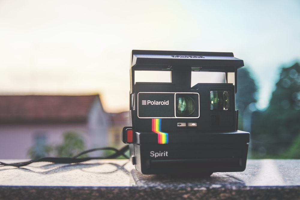 black Polaroid Spirit land camera on gray surfac e