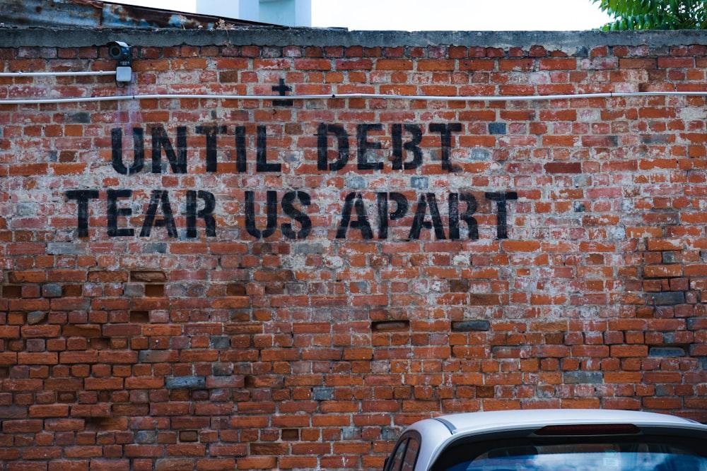 until debt tear us apart brick wall vandal