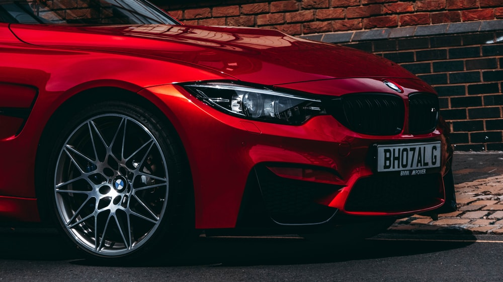 red BMW vehicle park on road