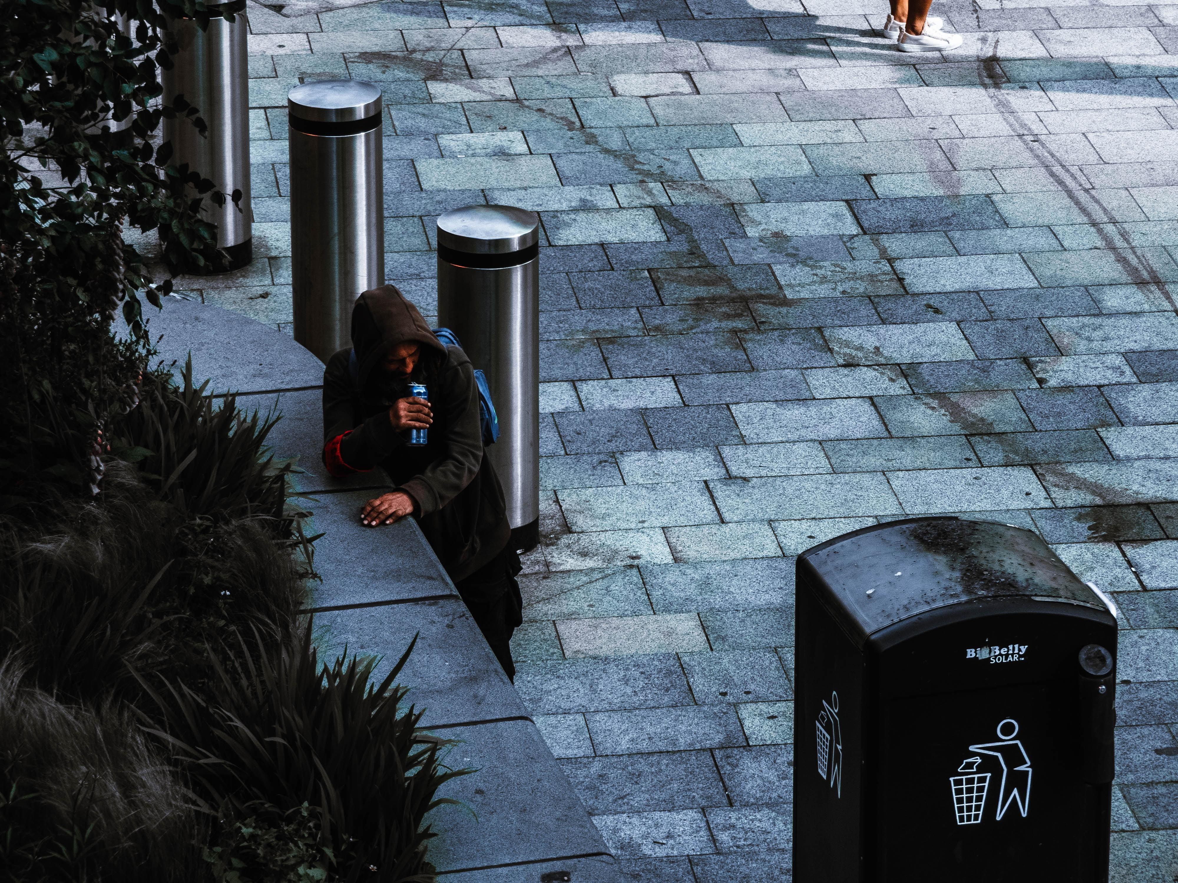 man standing near black trash bin