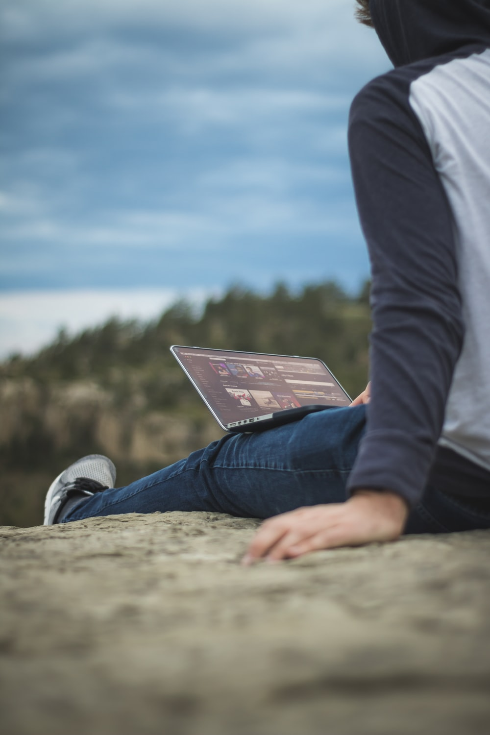 man sitting on cliff with laptop on legs