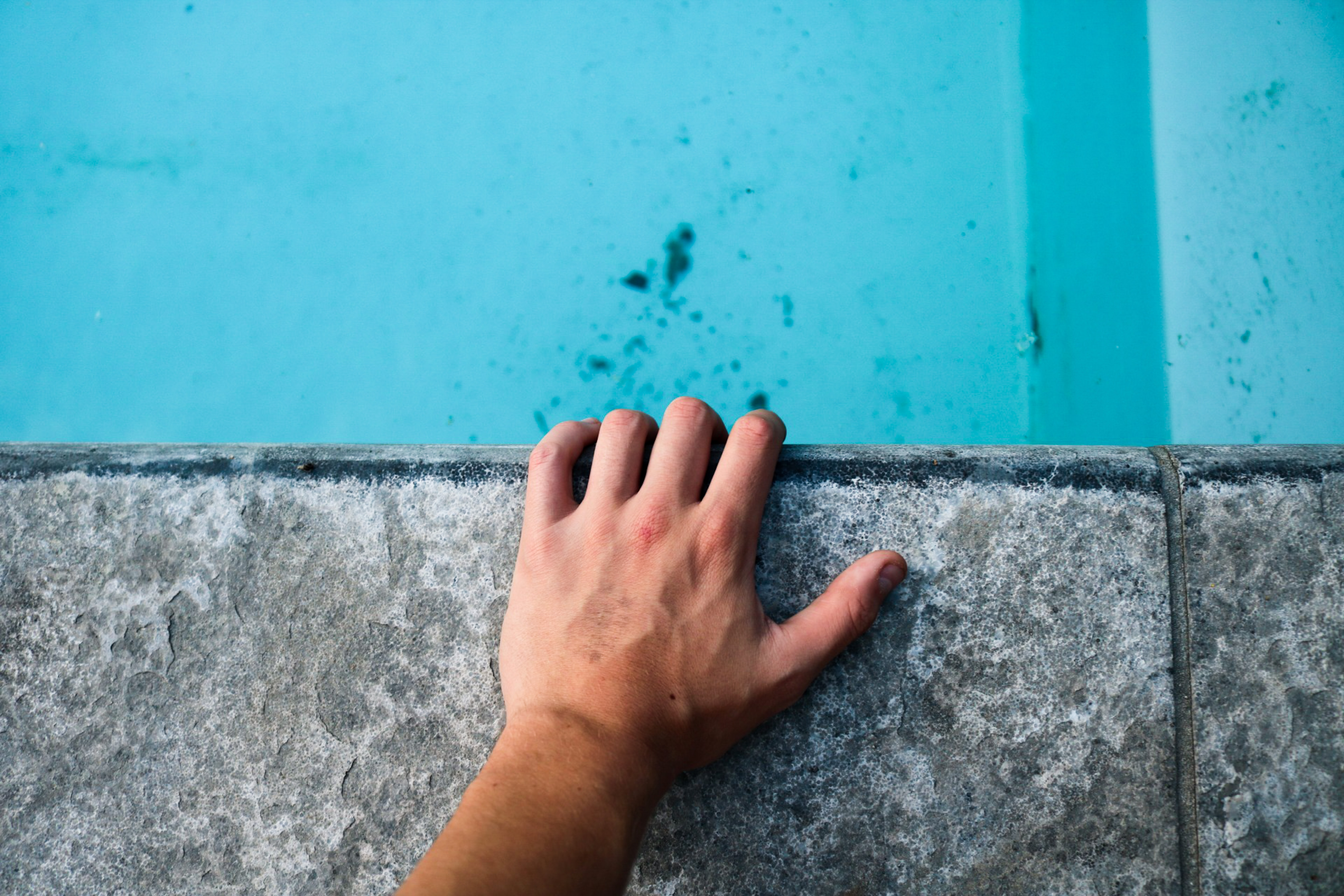 person's left hand holding gray concrete surface