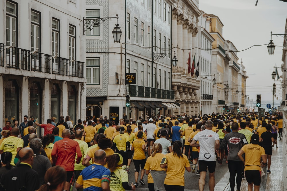 crowd of people running on the street near buildings during daytime