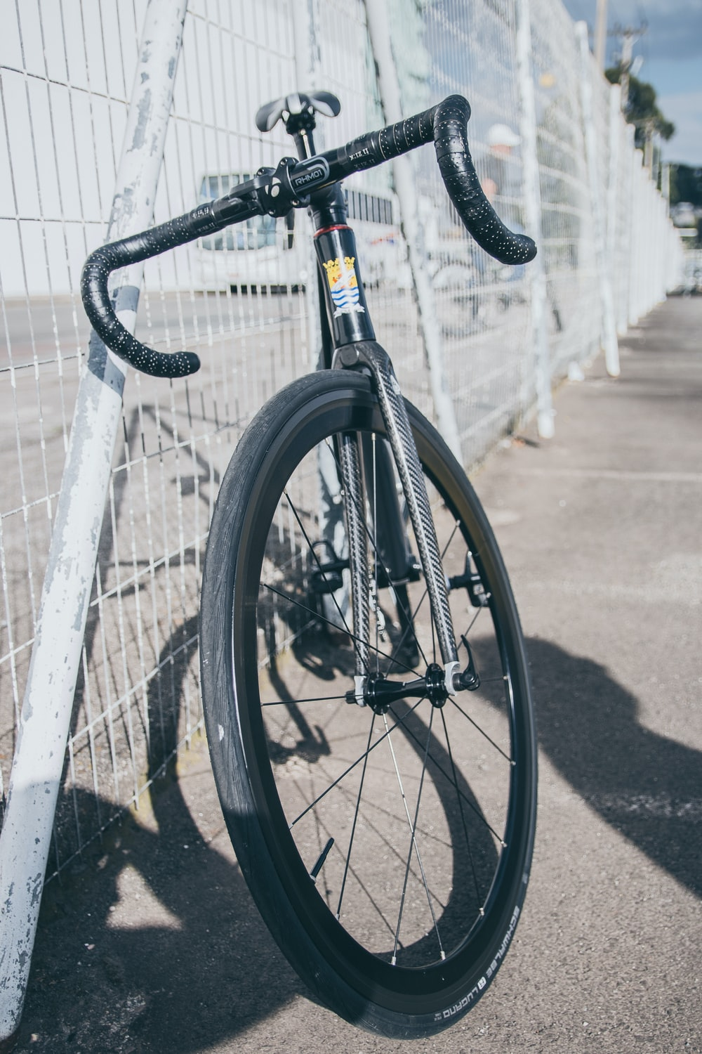 black and white road bike parked beside metal fence