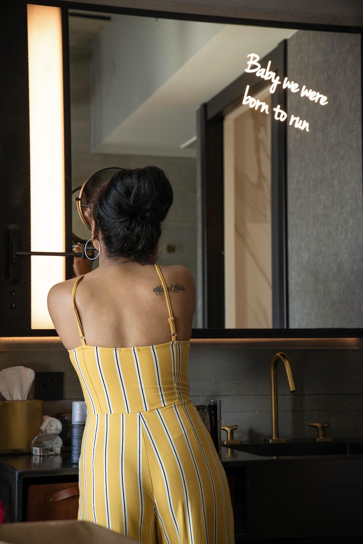 woman wearing yellow spaghetti strap jumpsuit near mirror