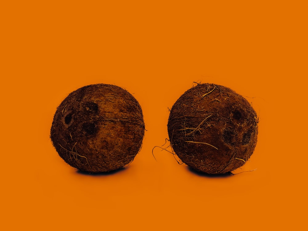 two coconut shells on orange surface