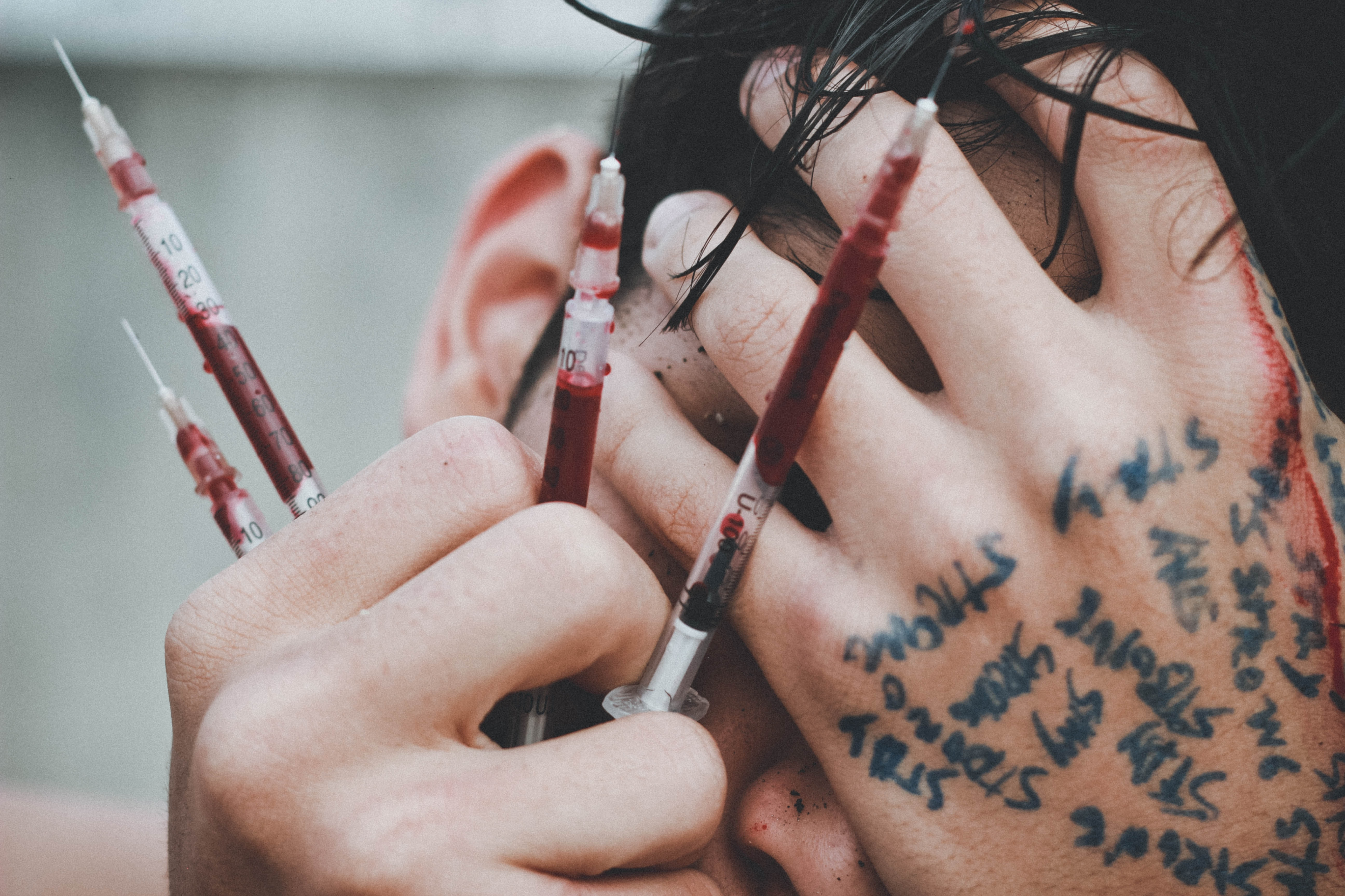 man holding syringes of red stain