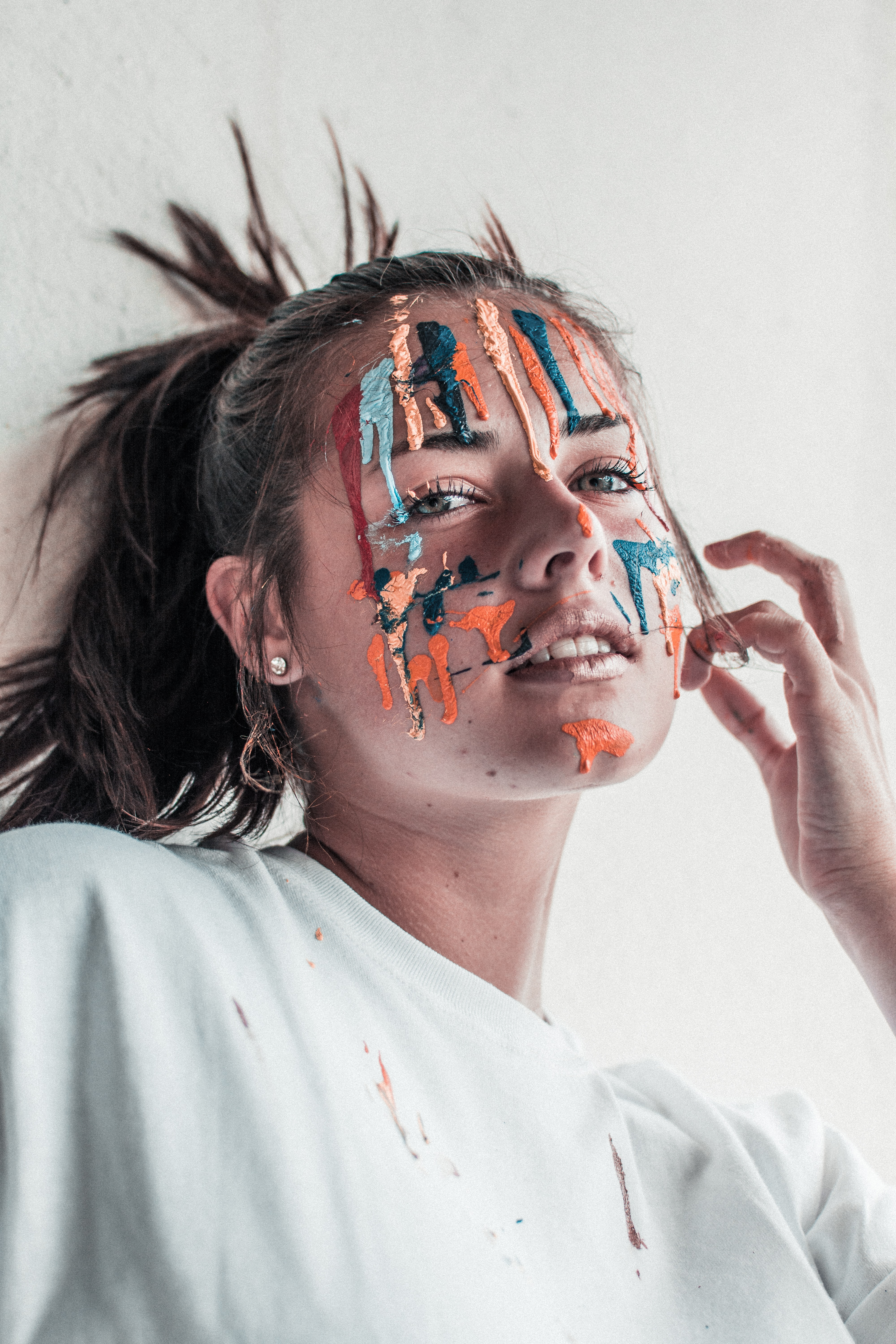woman leaning on wall with paint on face