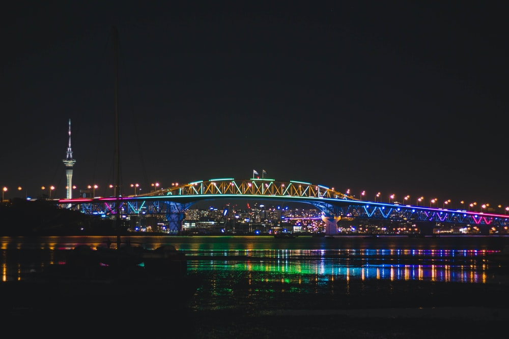 bridge with lights over body of water at nighttime